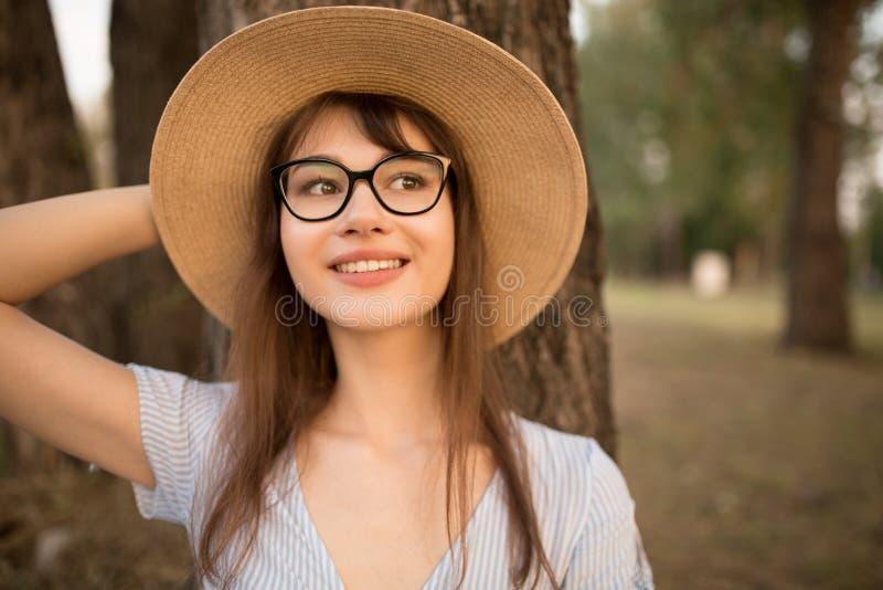 Portrait d'une jeune femme attirante en parc Brune heureuse dans un chapeau avec les verres et la robe photos libres de droits