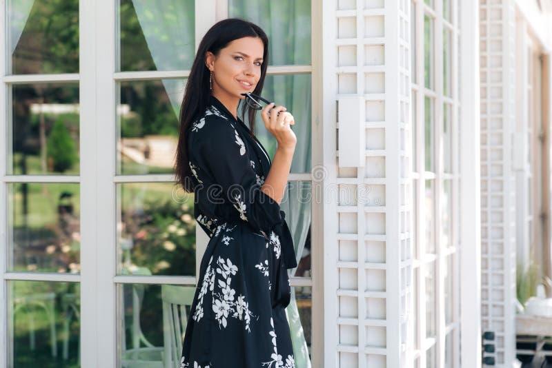 Portrait d'une jeune femme attirante mignonne dans des vêtements en soie tenant ses propres verres dans sa main Le beau débutant images stock
