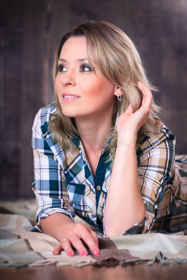 Portrait d'une jeune femme attirante se trouvant sur la couverture de plaid, plan rapproché photos stock