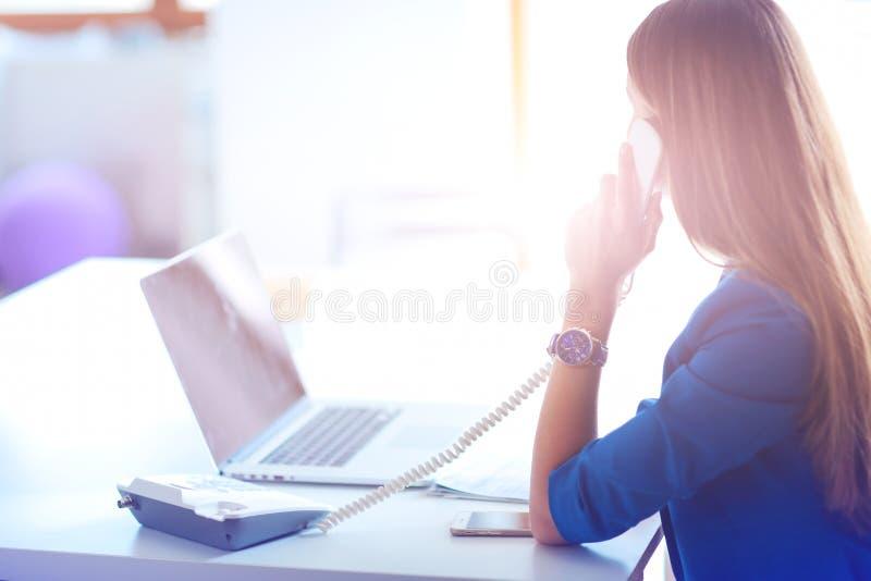 Portrait d'une jeune femme au téléphone devant un ordinateur portable photographie stock libre de droits
