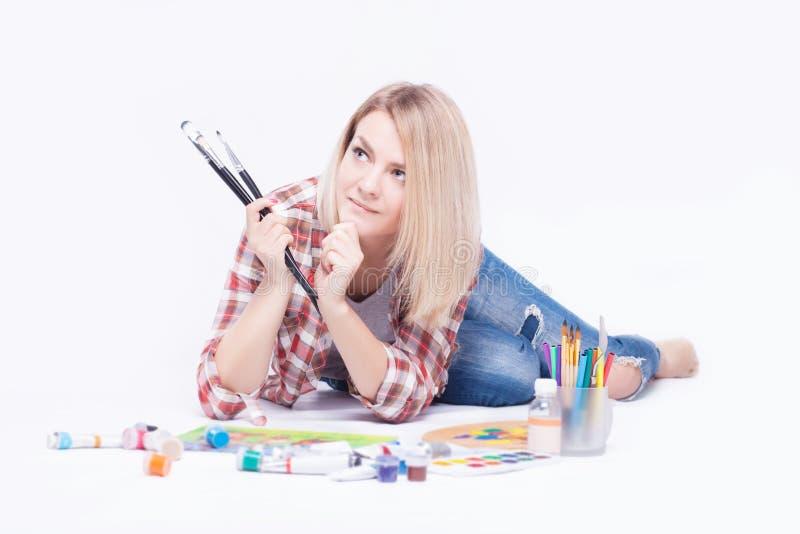 Portrait d'une jeune femme avec des brosses dans des ses mains dans le studio photo stock