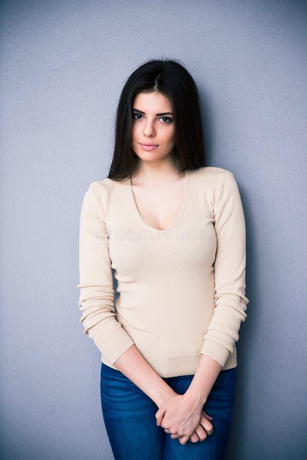 Portrait d'une jeune femme avec du charme au-dessus de fond gris photographie stock libre de droits