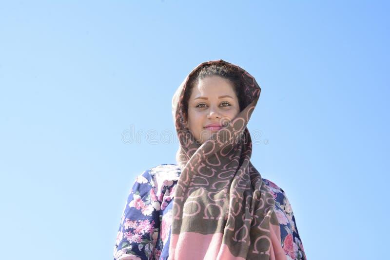 Portrait d'une jeune femme avec l'écharpe devant le ciel bleu photo stock