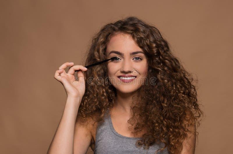 Portrait d'une jeune femme avec le mascara de maquillage dans un studio sur le fond brun photo stock