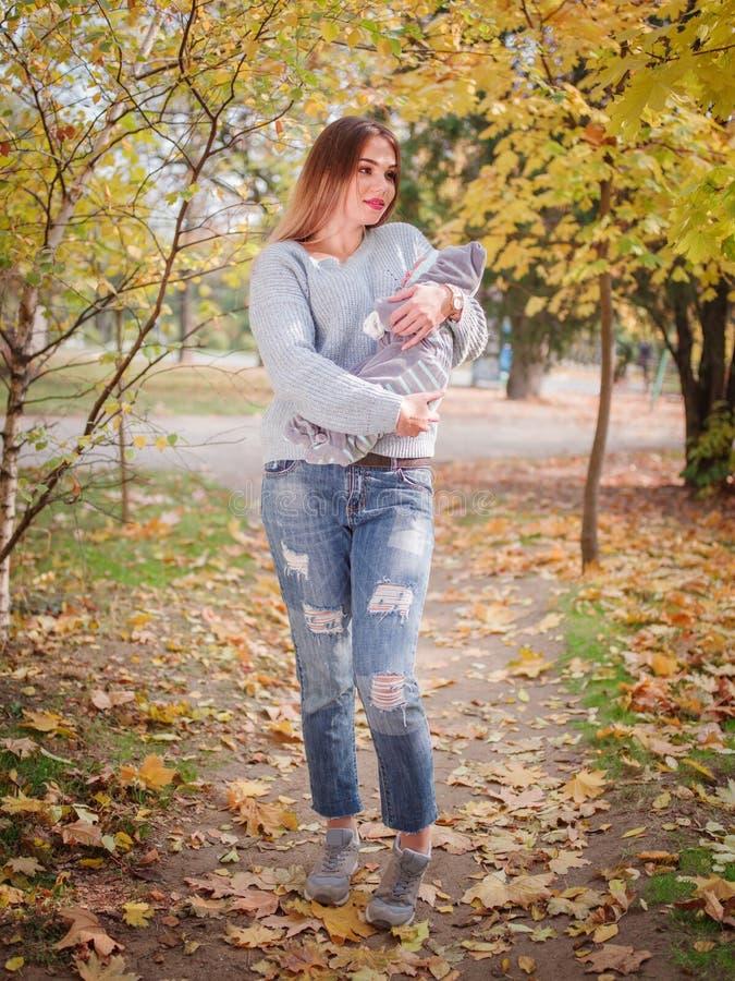 Portrait d'une jeune femme avec un bébé dans des ses bras en parc photo stock
