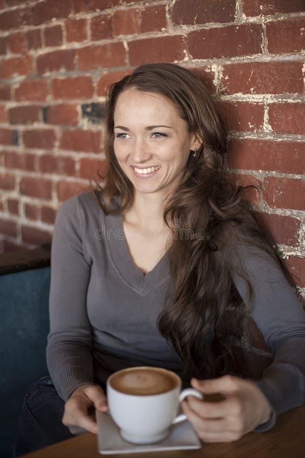Jeune femme avec de beaux yeux verts avec la tasse de café blanc photo libre de droits