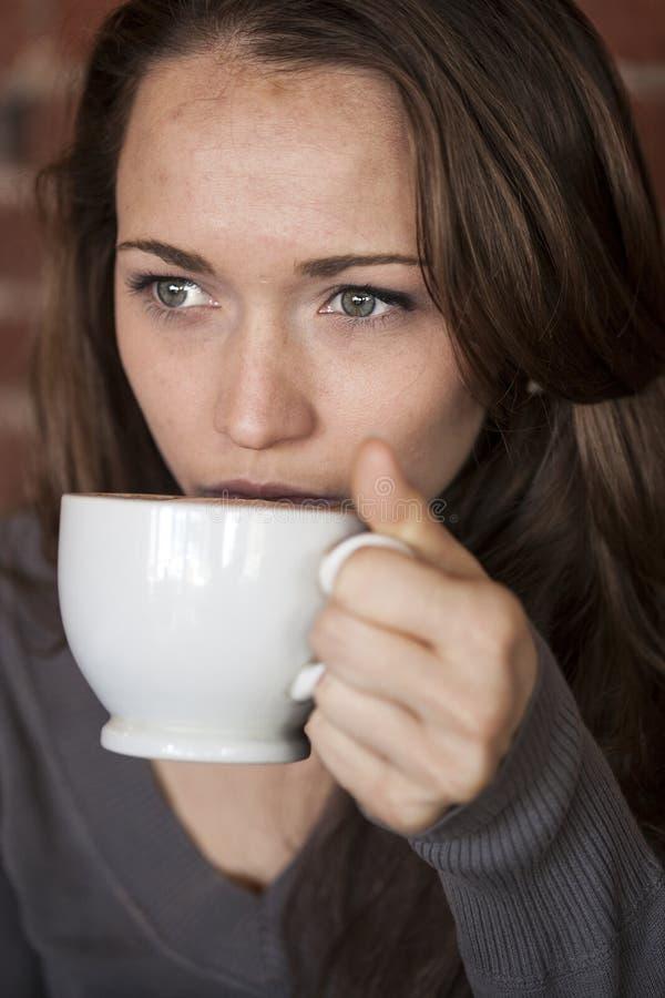 Jeune femme avec de beaux yeux verts avec la tasse de café blanc photographie stock