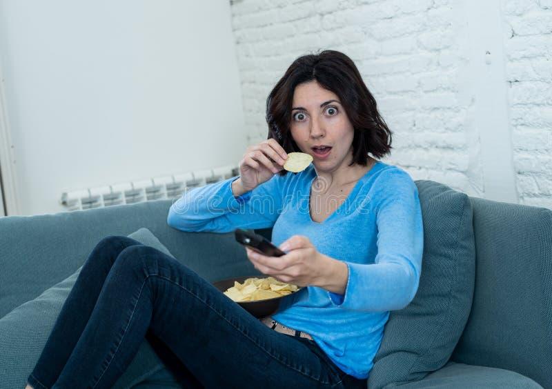 Portrait d'une jeune femme ayant l'air effrayée et choquée en regardant la télévision Expression humaine et émotion photo libre de droits
