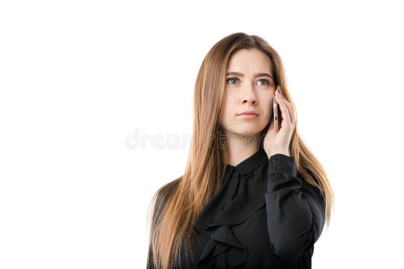 Portrait d'une jeune femme caucasienne dans une chemise noire et de longs cheveux débordants utilisant le téléphone main-se te image stock
