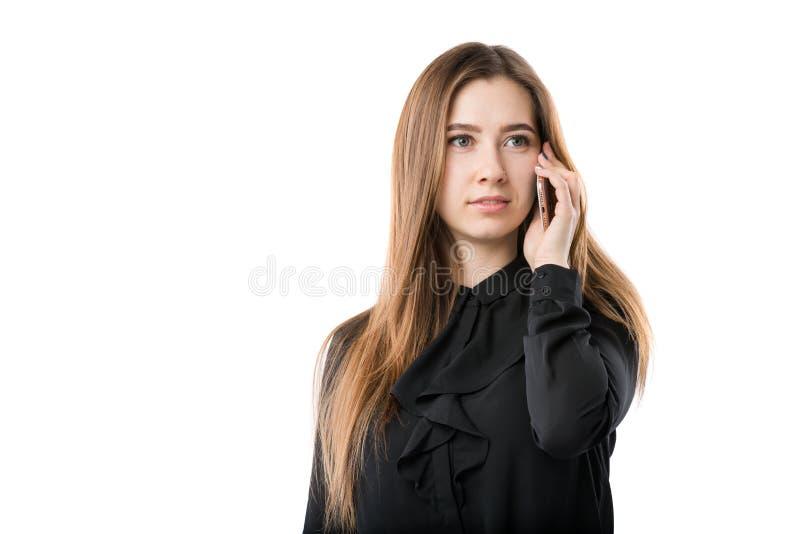 Portrait d'une jeune femme caucasienne dans une chemise noire et de longs cheveux débordants utilisant le téléphone main-se te photos stock