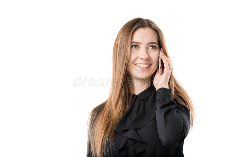 Portrait d'une jeune femme caucasienne dans une chemise noire et de longs cheveux débordants utilisant le téléphone main-se te photo libre de droits