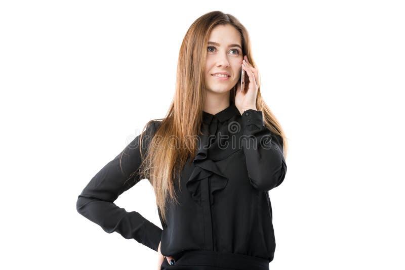 Portrait d'une jeune femme caucasienne dans une chemise noire et de longs cheveux débordants utilisant le téléphone main-se te photographie stock