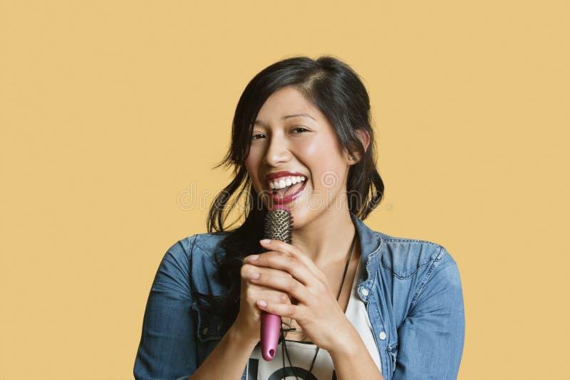 Portrait d'une jeune femme chantant dans une brosse à cheveux au-dessus de fond coloré photos libres de droits
