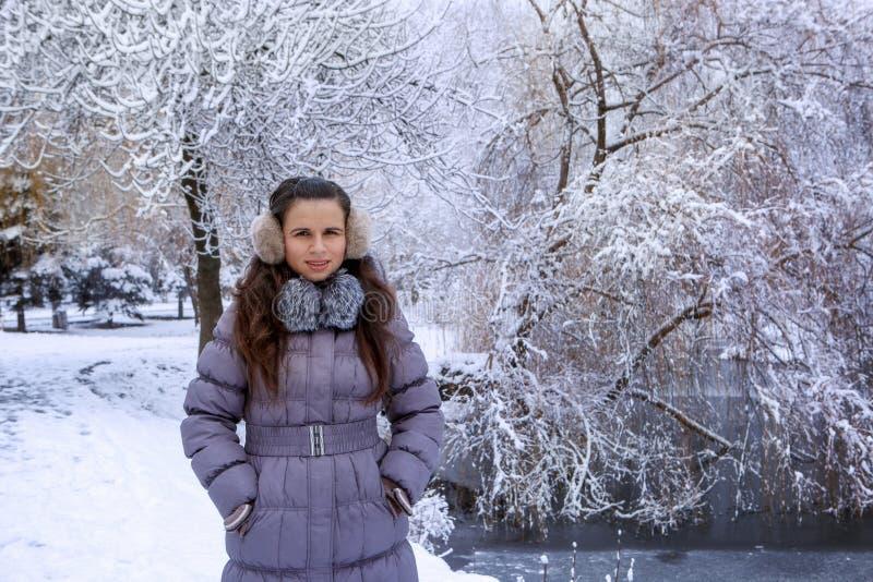 Portrait d'une jeune femme dans des bouche-oreilles d'hiver photographie stock