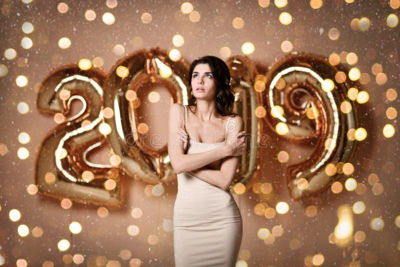 Portrait d'une jeune femme dans la robe nue s sous le boke ayant l'amusement avec le ballon de l'or 2019 image libre de droits