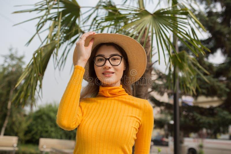 Portrait d'une jeune femme dans la ville Palmiers ? l'arri?re-plan Femme intelligente heureuse avec le chapeau en verre I images stock