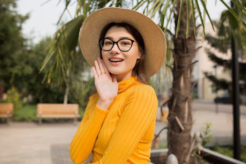 Portrait d'une jeune femme dans la ville Palmiers ? l'arri?re-plan Femme intelligente heureuse avec le chapeau en verre I photo libre de droits