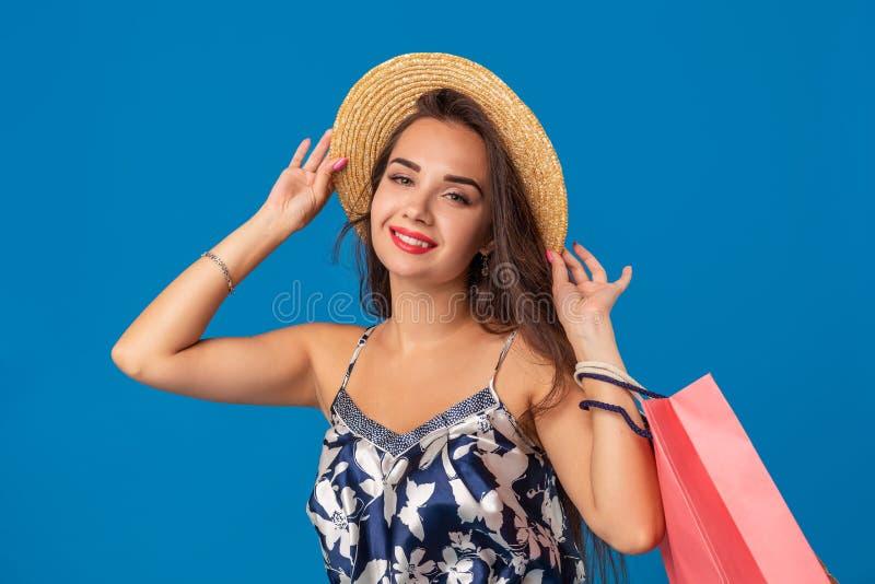 Portrait d'une jeune femme dans le chapeau d'été tenant des paniers et regardant l'appareil-photo d'isolement au-dessus du fond b photographie stock libre de droits