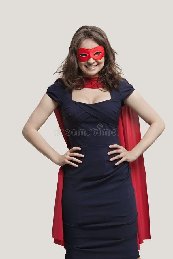 Portrait d'une jeune femme dans le costume de super héros au-dessus du fond gris images libres de droits