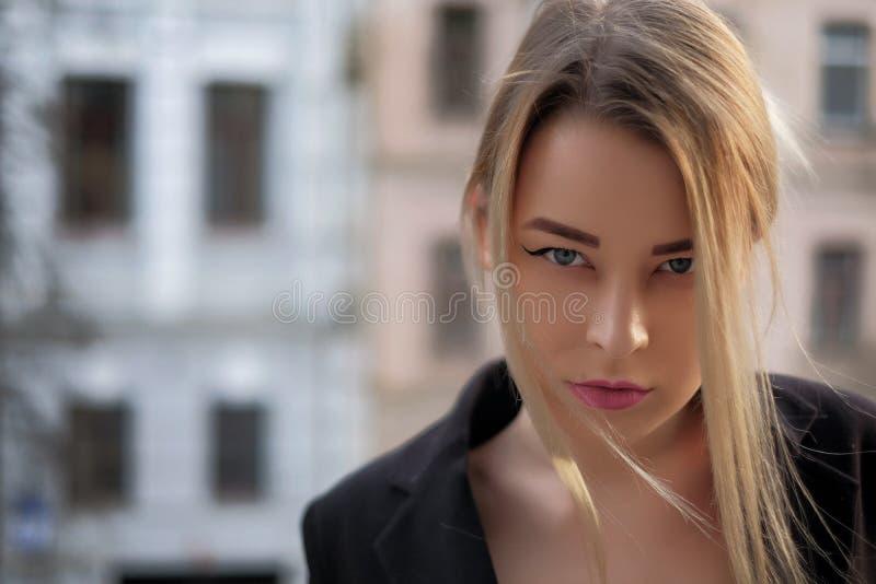 Portrait d'une jeune femme dans un plan rapproché noir de costume sur un fond d'une ville trouble dans les rayons du coucher de s photographie stock libre de droits