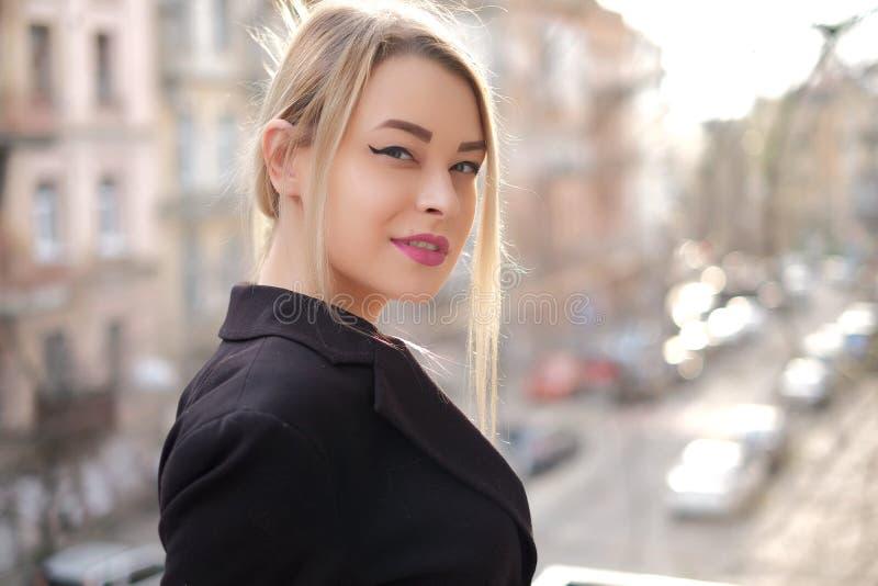 Portrait d'une jeune femme dans un plan rapproché noir de costume sur un fond d'une ville trouble dans les rayons du coucher de s images stock