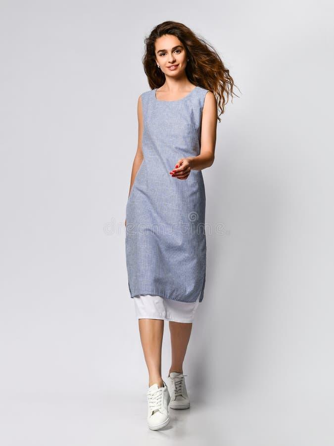 Portrait d'une jeune femme de brune dans une robe l?g?re bleue posant sur un fond clair, mode d'?t?, se pr?parant ? une date images libres de droits