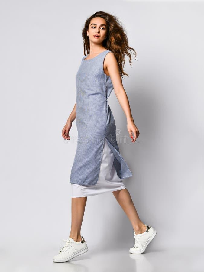Portrait d'une jeune femme de brune dans une robe l?g?re bleue posant sur un fond clair, mode d'?t?, se pr?parant ? une date photo libre de droits