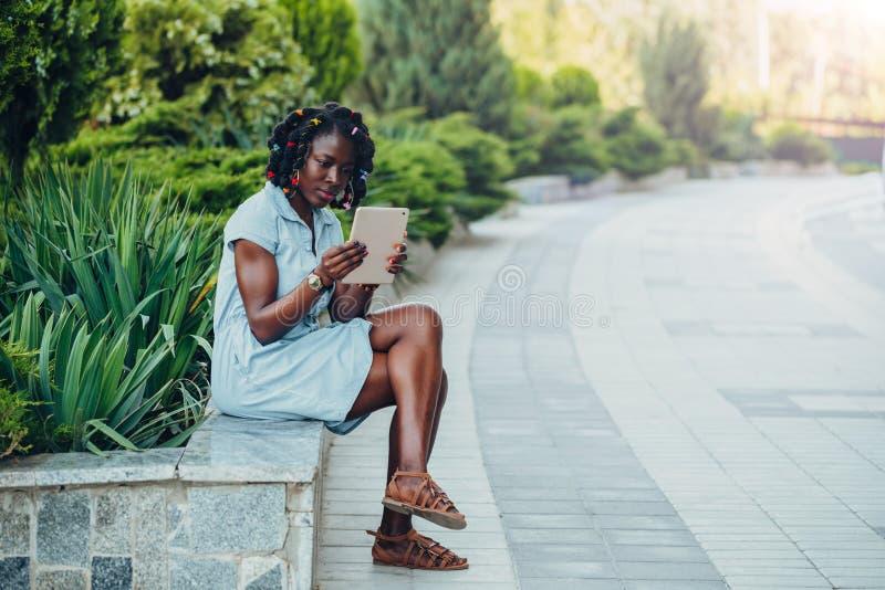 Portrait d'une jeune femme de couleur de sourire africaine s'asseyant en parc et à l'aide d'un comprimé numérique regardant l'écr image stock