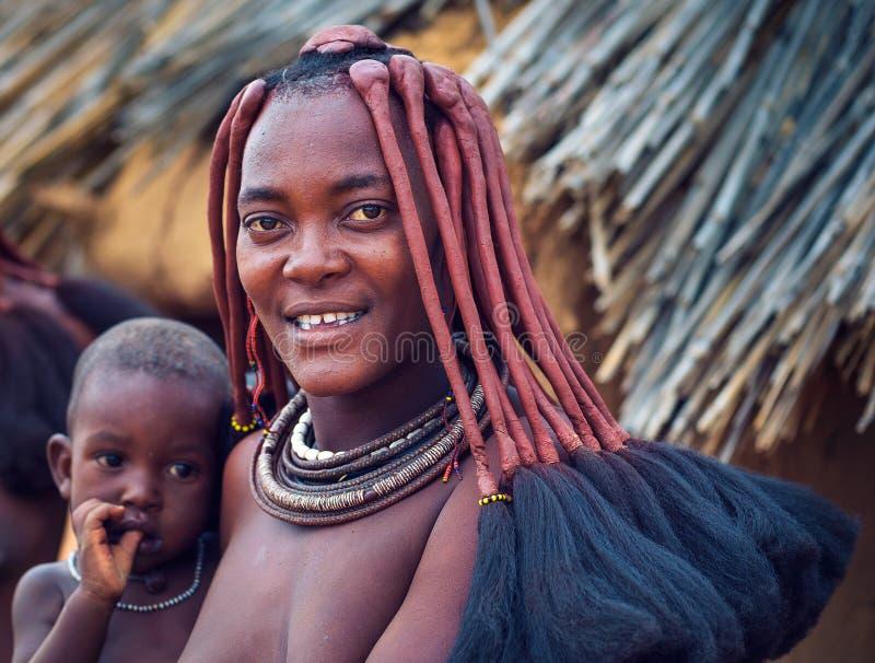 Portrait d'une jeune femme de himba avec son enfant portant la coiffure traditionnelle photo stock