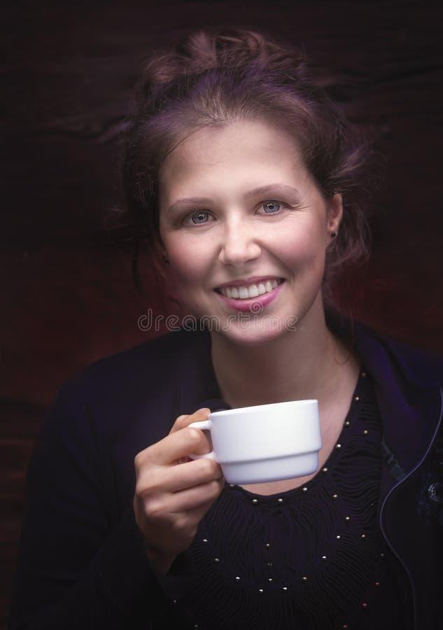 Portrait d'une jeune femme de sourire avec une tasse blanche image libre de droits