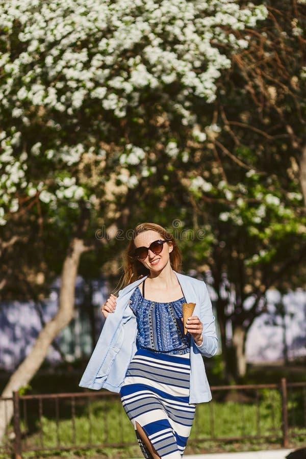 Portrait d'une jeune femme de sourire dans des lunettes de soleil avec la crème glacée dans des ses mains dehors photos stock