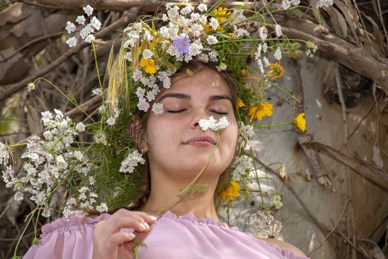 Portrait d'une jeune femme de sourire dans une guirlande des fleurs reniflant un plan rapproch? de fleur images stock