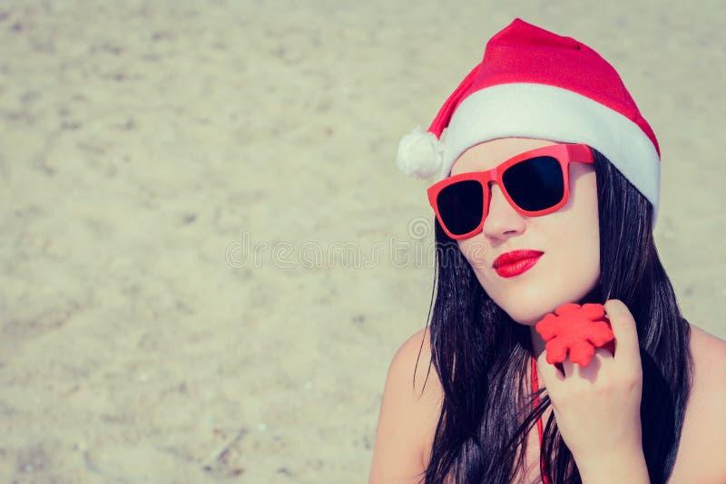 Portrait d'une jeune femme de sourire en chapeau et sungla de Santa Claus image libre de droits