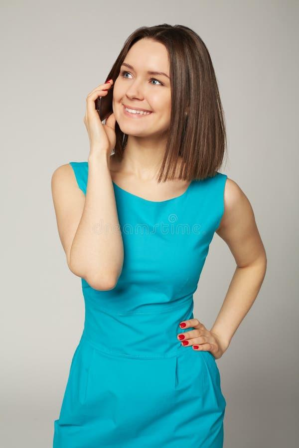 Portrait d'une jeune femme de sourire parlant au téléphone portable photographie stock libre de droits