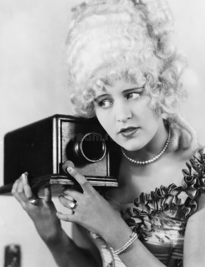 Portrait d'une jeune femme employant un appareil-photo (toutes les personnes représentées ne sont pas plus long vivantes et aucun photo stock