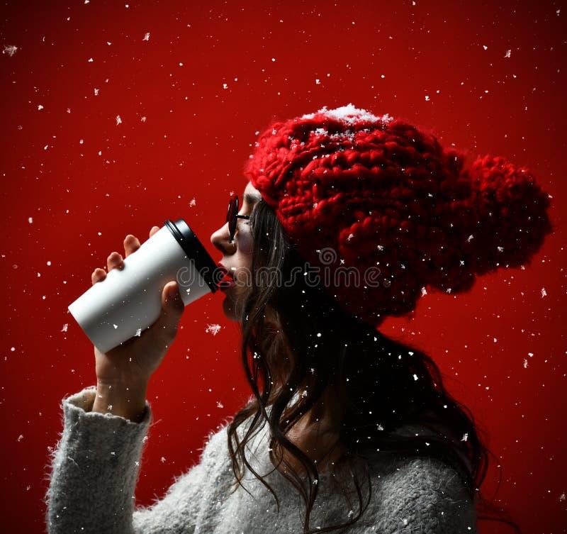 Portrait d'une jeune femme en café potable de tissu d'hiver photo stock