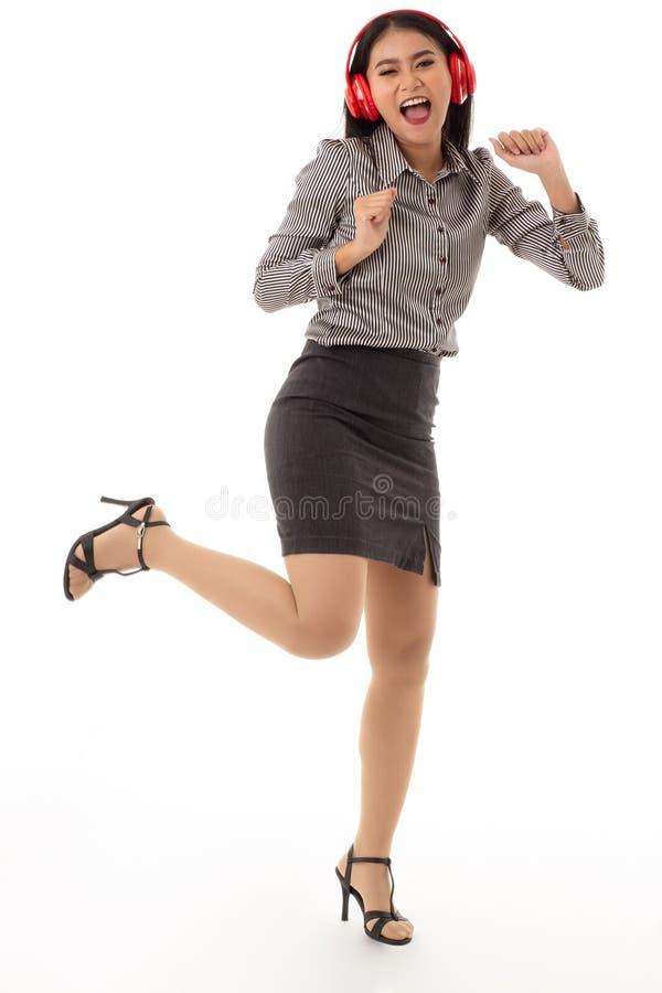 Portrait d'une jeune femme enthousiaste utilisant les écouteurs rouges se tenant avec des gestes joyeux d'isolement sur le fond b images stock
