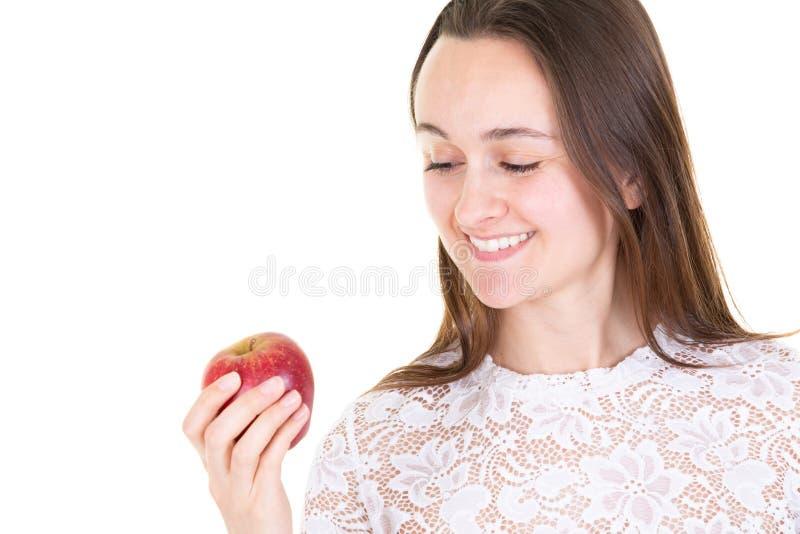 Portrait d'une jeune femme gaie mangeant la pomme rouge photo libre de droits