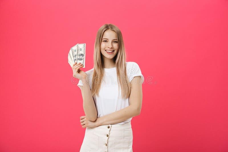 Portrait d'une jeune femme gaie tenant des billets de banque d'argent et de la célébration d'isolement au-dessus du fond rose photographie stock libre de droits