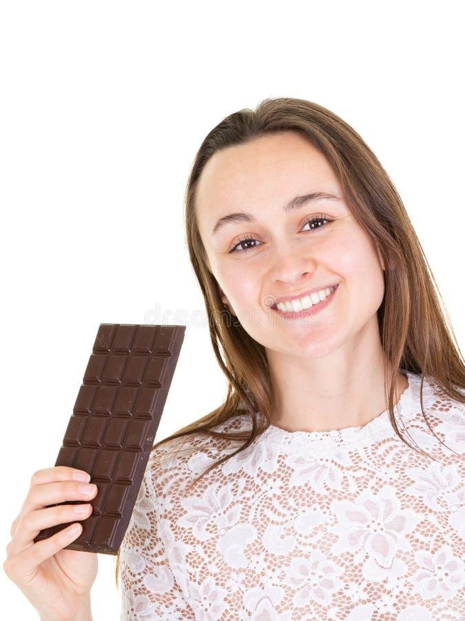 Portrait d'une jeune femme heureuse tenant la barre de chocolat photographie stock libre de droits
