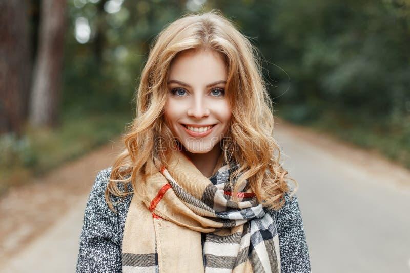 Portrait d'une jeune femme mignonne joyeuse avec un sourire avec des yeux bleus dans un manteau élégant avec une écharpe élégante images stock
