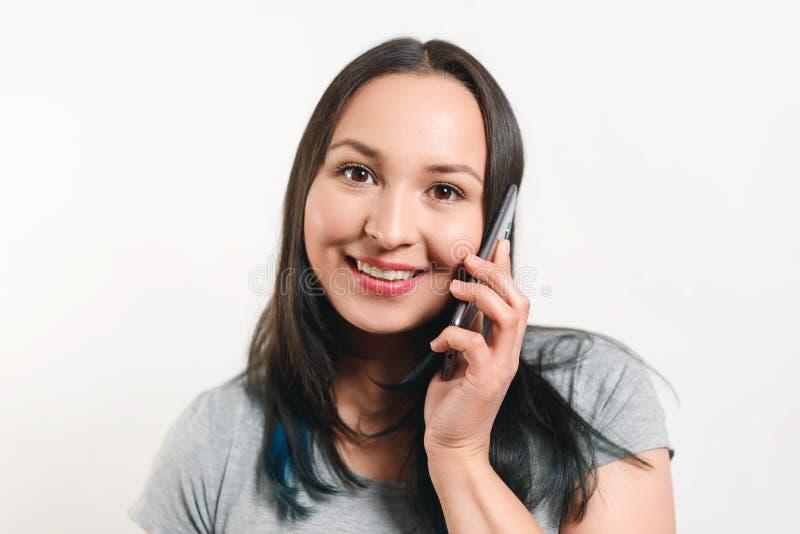Portrait d'une jeune femme occasionnelle de sourire de brune parlant au téléphone portable, au-dessus du fond blanc photos stock
