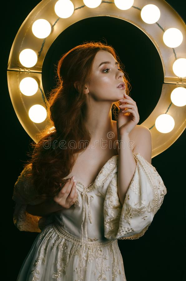 Portrait d'une jeune femme rousse dans une robe de cendre de vintage avec les épaules ouvertes sur un fond des lumières Une princ photographie stock