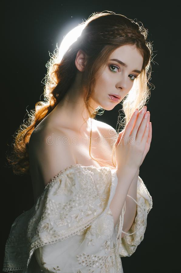 Portrait d'une jeune femme rousse de prière dans la robe de cendre de vintage avec les épaules ouvertes sur un fond noir dans le  images stock