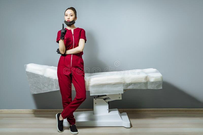 Portrait d'une jeune femme sérieuse dans l'uniforme et des gants près du divan sur un fond gris photo stock