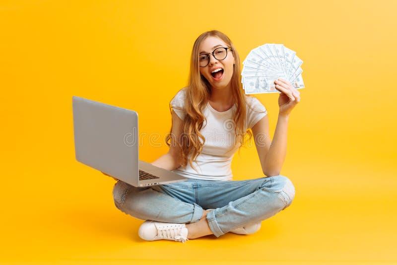 Portrait d'une jeune femme, se reposant sur le plancher, utilisant un ordinateur portable portatif et tenant l'argent dans sa mai photo stock