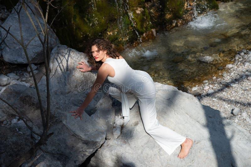 Portrait d'une jeune femme se trouvant sur les cailloux en pierre dans les montagnes images libres de droits