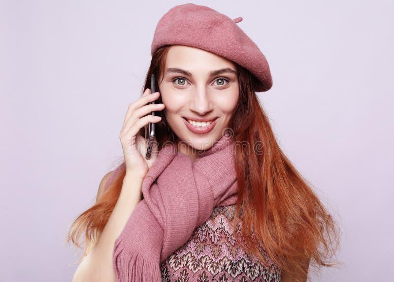 Portrait d'une jeune femme utilisant l'équipement rose parlant au téléphone portable image libre de droits