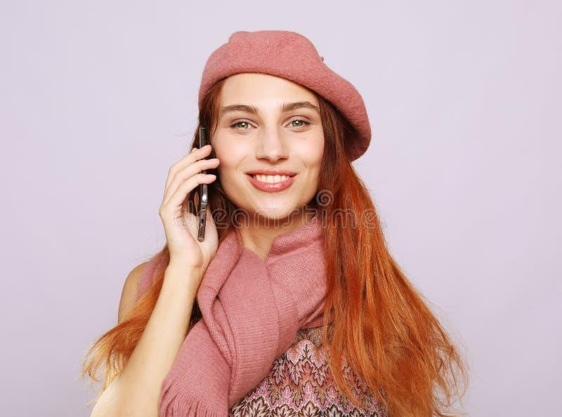 Portrait d'une jeune femme utilisant l'équipement rose parlant au téléphone portable photos stock