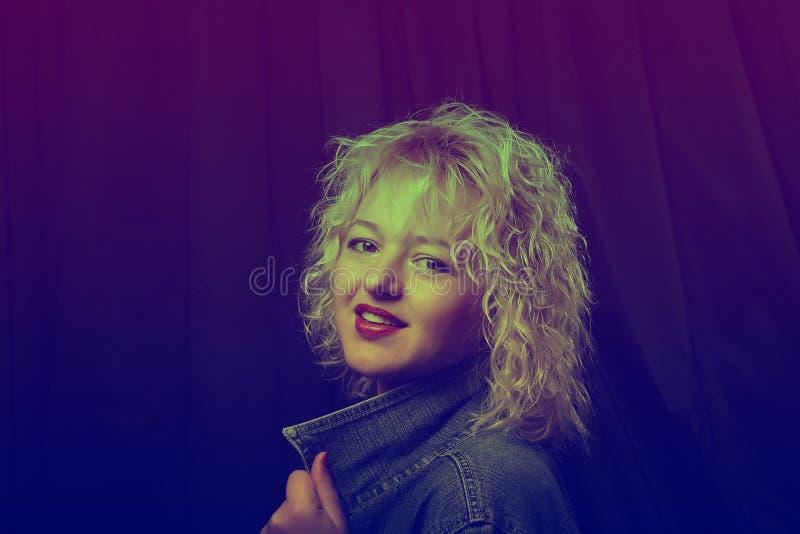 Portrait d'une jeune fille ?l?gante avec des verres dans la lampe au n?on Beau femme blond avec les languettes rouges La photo a  images stock